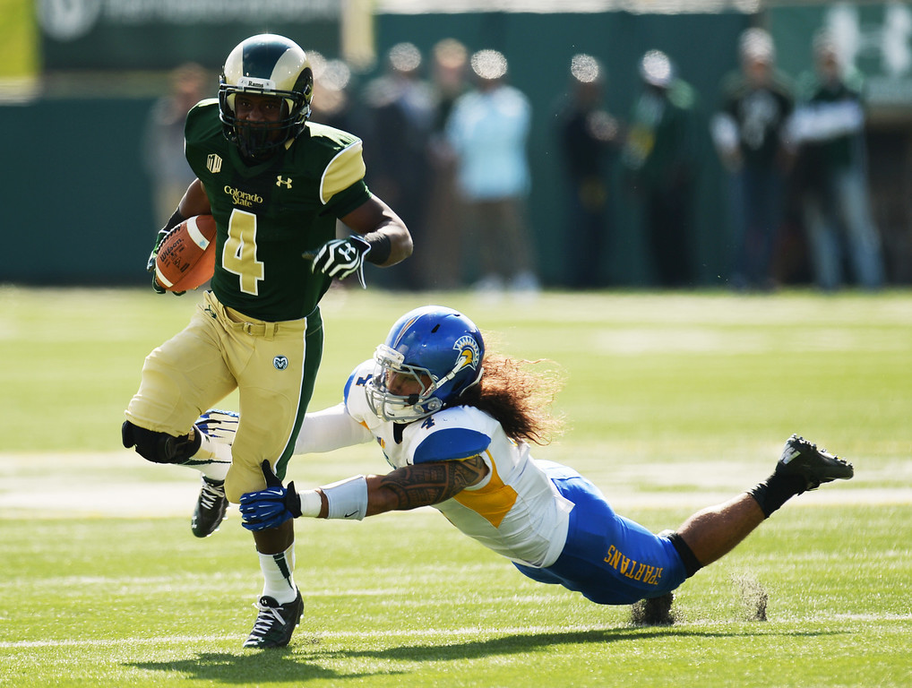 . FORT COLLINS, CO - OCTOBER 12 : Charles Lovett of Colorado State (4) escapes a tackle by Christian Tago of San Jose State (4) in the 1st quarter of the game at Hughes Stadium. Fort Collins. Colorado. October 12, 2013. San Jose won 34-27. (Photo by Hyoung Chang/The Denver Post)