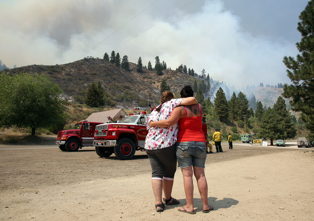 . Kylie Rivera, right, and Trish Kiester embrace as they watch the Elk Complex fire burn above the Pine Resort, which Trish owns and where Kylie lives, on Monday, Aug. 12, 2013 in Pine, Idaho. (AP Photo/The Idaho Statesman, Joe Jaszewski)