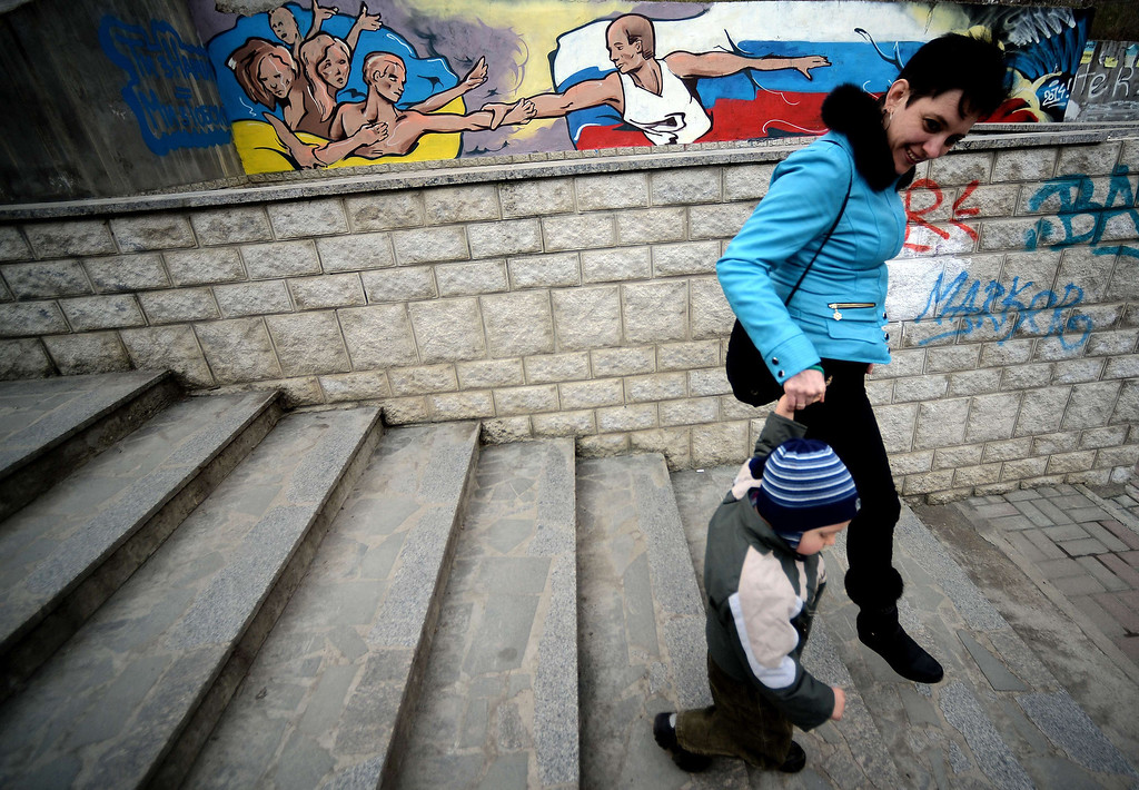 . A woman and a child walk by a mural depicting Russian president Vladimir Putin giving a hand to Ukrainians in downtown Simferopol on March 12, 2014. Pro-Moscow lawmakers in Crimea voted for independence from Ukraine on March 11 in a precursor to a referendum this weekend for the region to become part of Russia.  FILIPPO MONTEFORTE/AFP/Getty Images