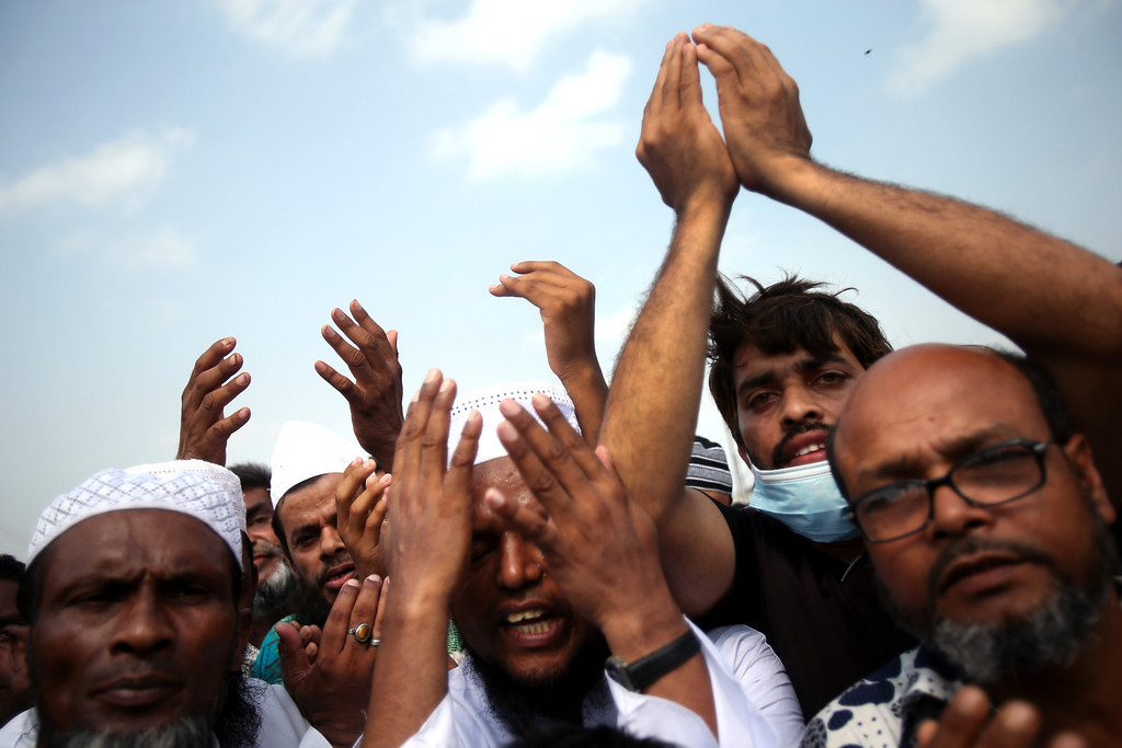 . A Muslim priest leads a crowd in prayers offered to unclaimed bodies from the building that collapsed last week in preparation for a mass burial on Wednesday, May 1, 2013, in Dhaka, Bangladesh. Several hundred people attended the mass funeral in a Dhaka suburb for 18 unidentified workers who died in the building housing garment factories that collapsed last week in the country\'s worst industrial disaster, killing at least 402 people and injuring 2,500.   (AP Photo/Wong Maye-E)