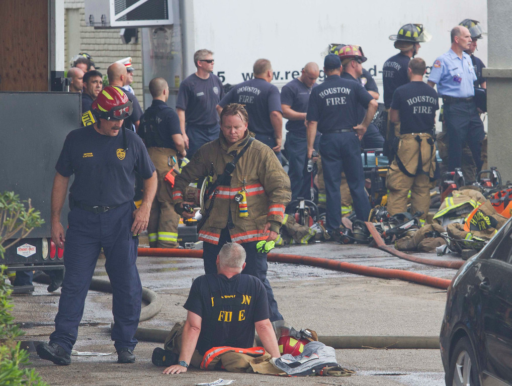 . Firefighters gather at the scene of a fire where four firefighters were killed battling a five-alarm blaze at a restaurant and hotel in southwest Houston May 31, 2013.     REUTERS/Richard Carson
