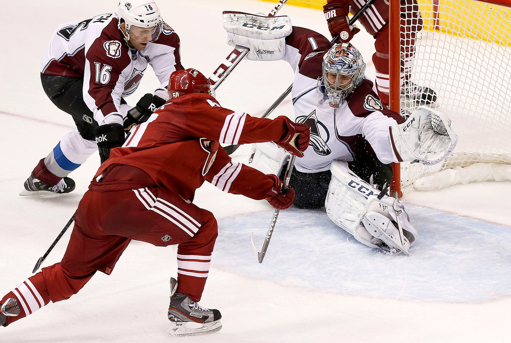 . Phoenix Coyotes\' Antoine Vermette (50) scores a goal in front of Colorado Avalanche\'s Semyon Varlamov (1), of Russia, as Cory Sarich (16) defends during the third period of an NHL hockey game Thursday, Nov. 21, 2013, in Glendale, Ariz.  The Avalanche defeated the Coyotes 4-3. (AP Photo/Ross D. Franklin)