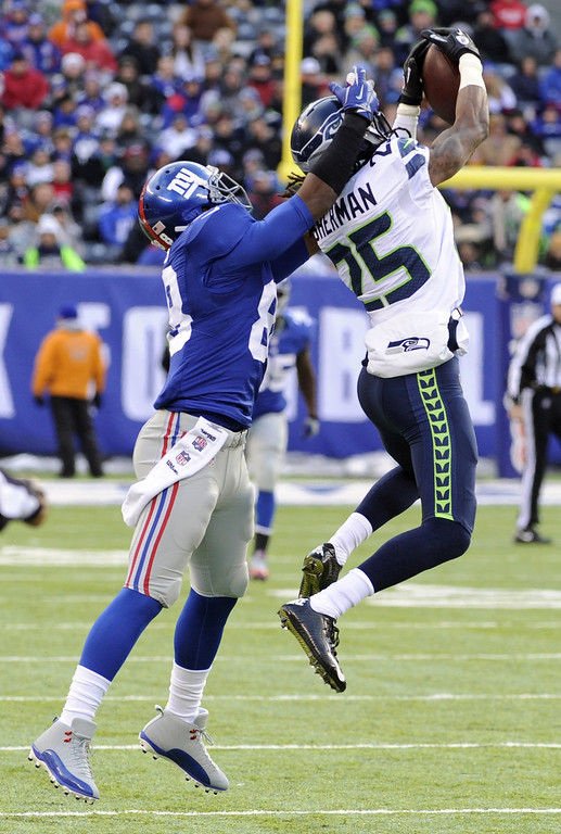 . Seattle Seahawks cornerback Richard Sherman, right, intercepts a pass from New York Giants quarterback Eli Manning intended for wide receiver Hakeem Nicks, left, during the first half of an NFL football game on Sunday, Dec. 15, 2013, in East Rutherford, N.J. (AP Photo/Bill Kostroun)