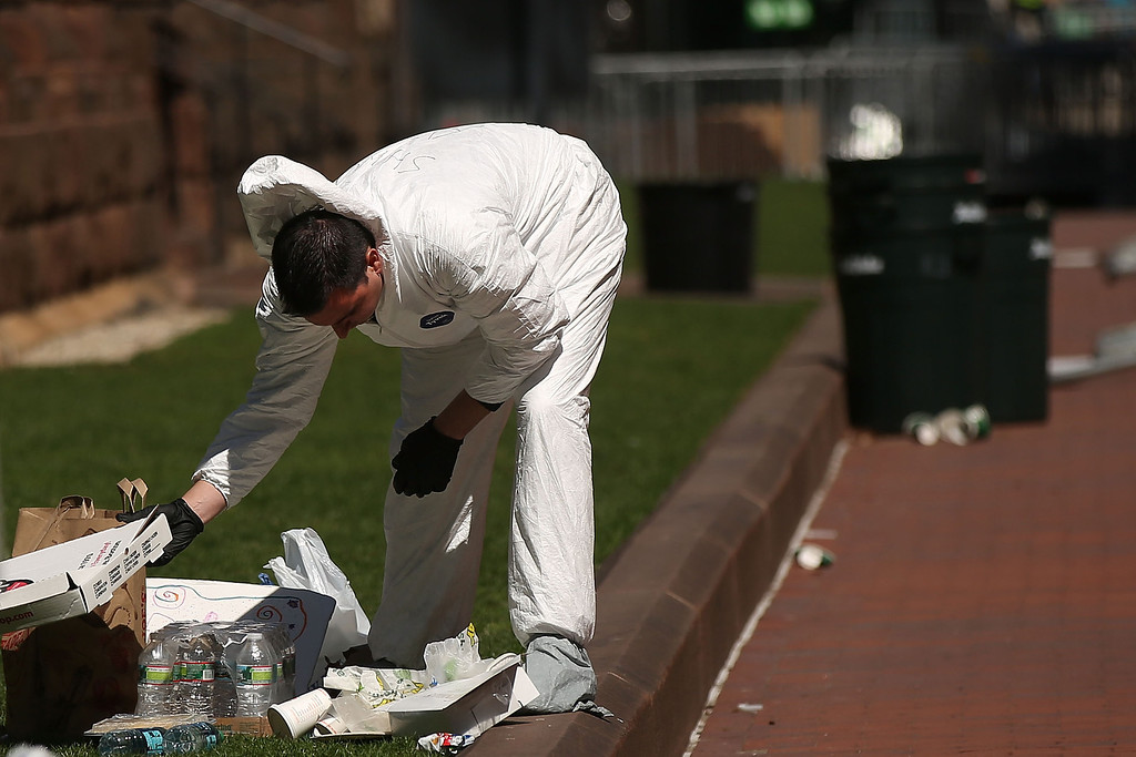 . A member of the Federal Bureau of Investigation (FBI) searches for clues near the scene of twin bombings at the Boston Marathon on April 17, 2013 in Boston, Massachusetts. The explosions, which occurred near the finish line of the 116-year-old Boston race on April 15, resulted in the deaths of three people with more than 170 others injured. Security has been heightened across the nation as the search continues for the person or people behind the bombings.  (Photo by Spencer Platt/Getty Images)