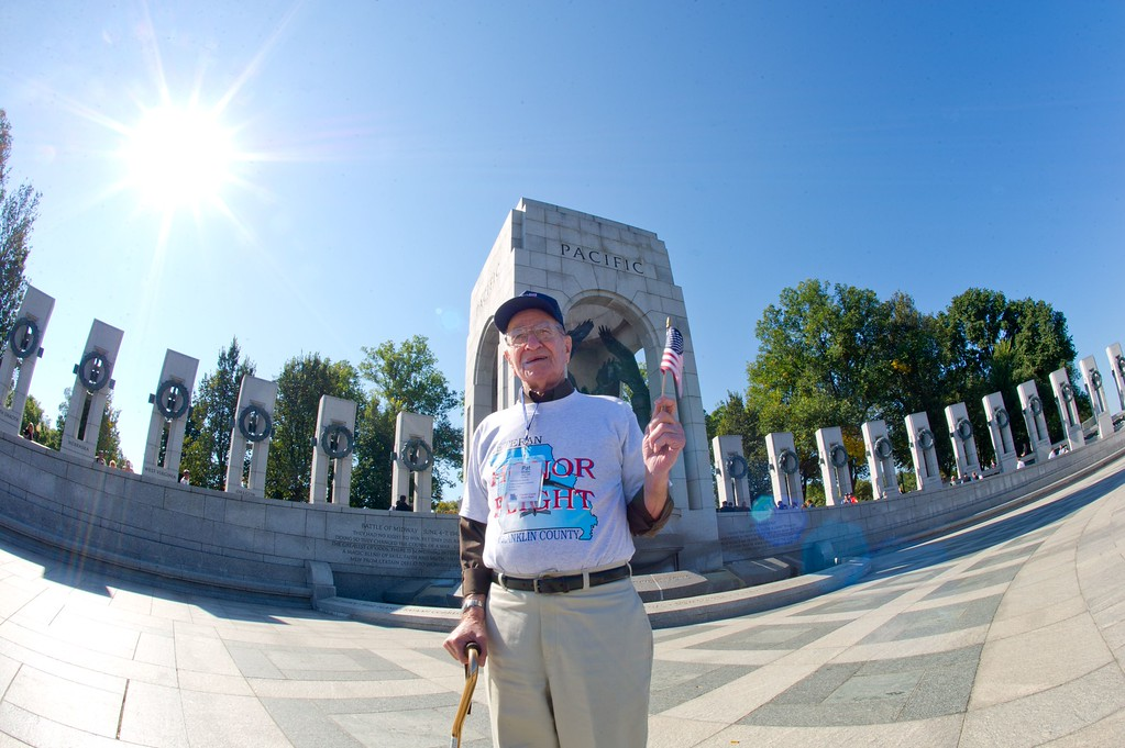 . US military veteran Pat Whalen, who served in the Pacific, waves a US flag as he makes his first visit to the World War II Memorial October 2, 2013 in Washington, DC. Veterans groups continue to visit the various war memorials even though they have been shuttered by the government shutdown.  AFP PHOTO / Karen  BLEIER/AFP/Getty Images