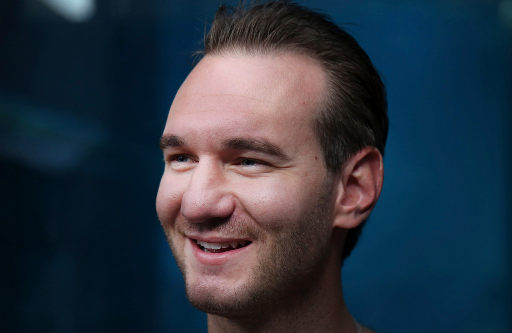 """. Nick Vujicic smiles at his camera crew before diving with sharks Thursday, Sept. 5, 2013 in Singapore. Vujicic, a Serbian Australian evangelist and motivational speaker born with tetra-amelia syndrome, a rare disorder characterized by the absence of all four limbs, is in the city-state to give a motivational talk and was visiting \""""The Shark Encounter at Marine Life Park\"""" at one of Singapore\'s main tourist attractions in Resorts World Sentosa. (AP Photo/Wong Maye-E)"""