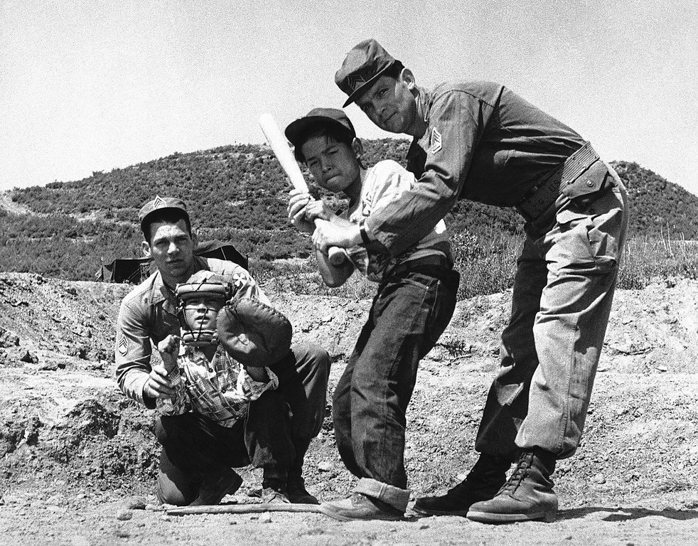 . The Korean Kids at the elementary school at Tongduch\'on ni, set up by GIs camped nearby in Korea on June 21, 1952, are learning baseball as well as their abc\'s for a well-rounded education. Sergeant Kenneth D. Henry, of Memphis, Mo., and Sergeant Jess R. Adkins, of Peru, Indiana, are giving instruction in the great American game to two of the older students of the school. (AP Photo)