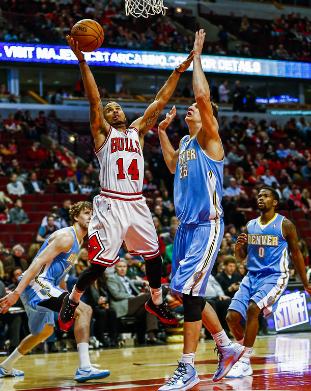 . Chicago Bulls guard D.J. Augustin (C-L) shoots in front of Denver Nuggets center Timofey Mozgov of Russia (C-R) in the second half of their NBA game at the United Center in Chicago, Illinois, USA, 21 February 2014. The Bulls defeated the Nuggets.  EPA/TANNEN MAURY