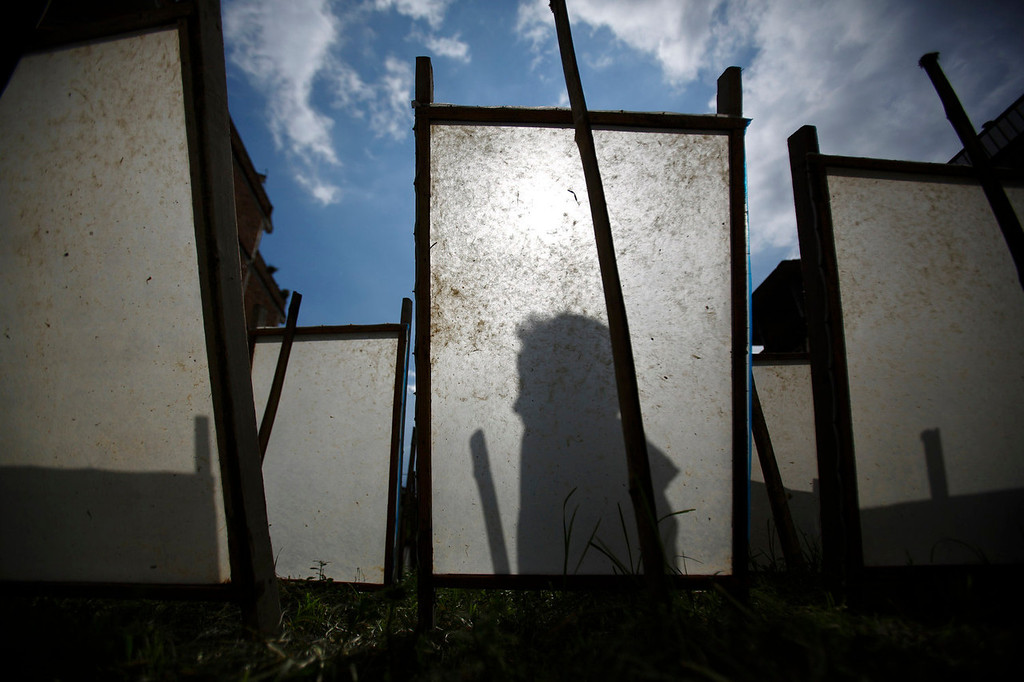 . The shadow of one of Arjun Nepali\'s sons is cast on a Handmade Nepali Lokta Paper kept to dry out in the sun after being produced at a factory in Bhaktapur July 17, 2013. According to Arjun he earns 300 Nepalese rupees ($3.15) a day working at a factory from which he runs his house and sends his three sons to a government school. Lokta papers are made up of fibrous inner bark of Lokta bushes that are found above 5,000 m above sea level. According to factory owner Shyam Hari Kadel most of the papers that he produced are exported to countries like Germany and Britain.  REUTERS/Navesh Chitrakar