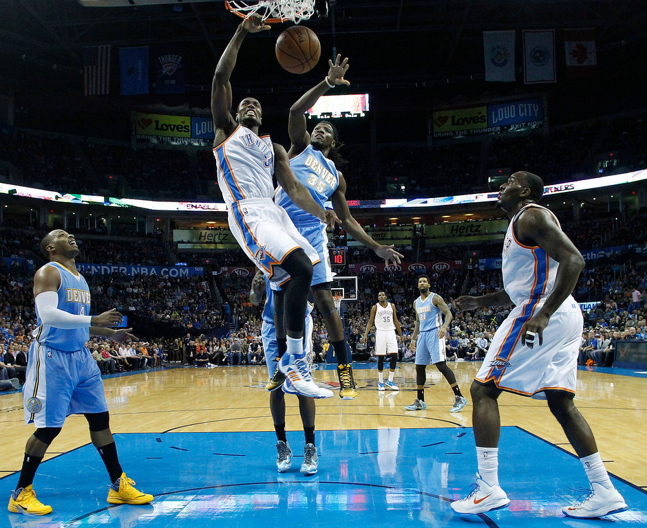 . Oklahoma City Thunder forward Serge Ibaka (9) dunks in front of Denver Nuggets forward Kenneth Faried (35) in the first quarter of an NBA basketball game in Oklahoma City, Monday, Nov. 18, 2013. Oklahoma City won 115-113. (AP Photo/Sue Ogrocki)