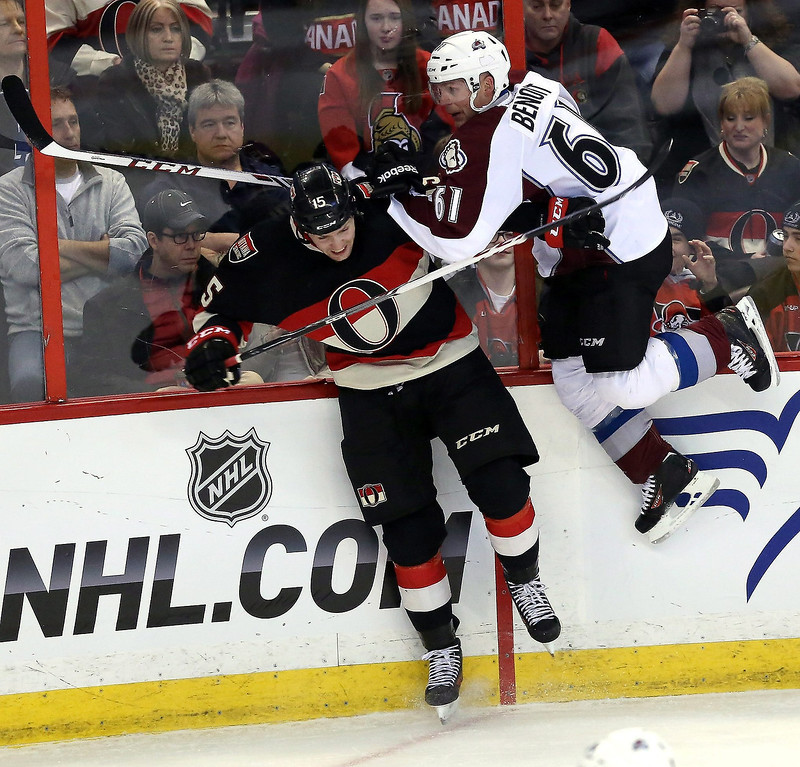 . Ottawa Senators\' Zack Smith (15) checks Colorado Avalanche\'s Andre Benoit (61) into the boards during first-period NHL hockey game action in Ottawa, Ontario, Sunday, March 16, 2014. (AP Photo/The Canadian Press, Fred Chartrand)