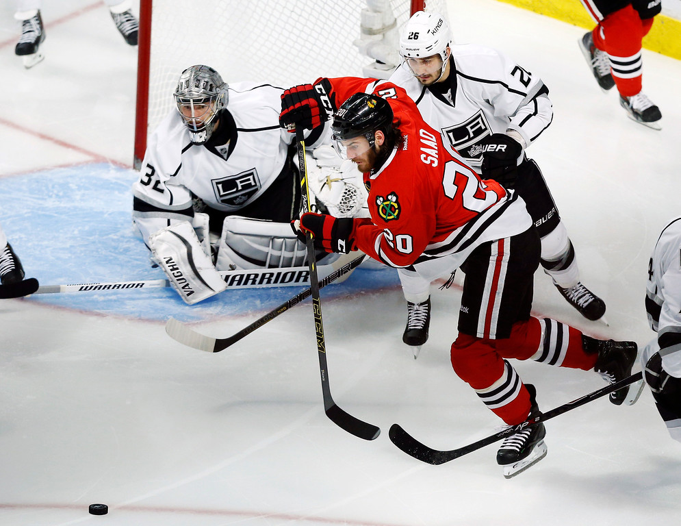 . Chicago Blackhawks left wing Brandon Saad (20) goes after the puck against Los Angeles Kings defenseman Slava Voynov (26) during the second period in Game 5 of the Western Conference finals in the NHL hockey Stanley Cup playoffs Wednesday, May 28, 2014, in Chicago. (AP Photo/Andrew A. Nelles)