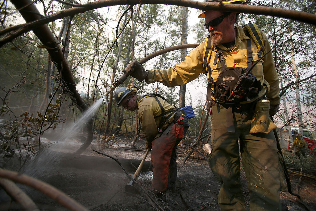 . David Hartman, left, and Scott Calderwood, both with the Pagosa Fire Protection District in Colo., mop up part of the 111,000 acre Elk Fire Complex near Pine, Idaho on Wednesday, August, 14, 2013. (AP Photo/Times-News, Ashley Smith)