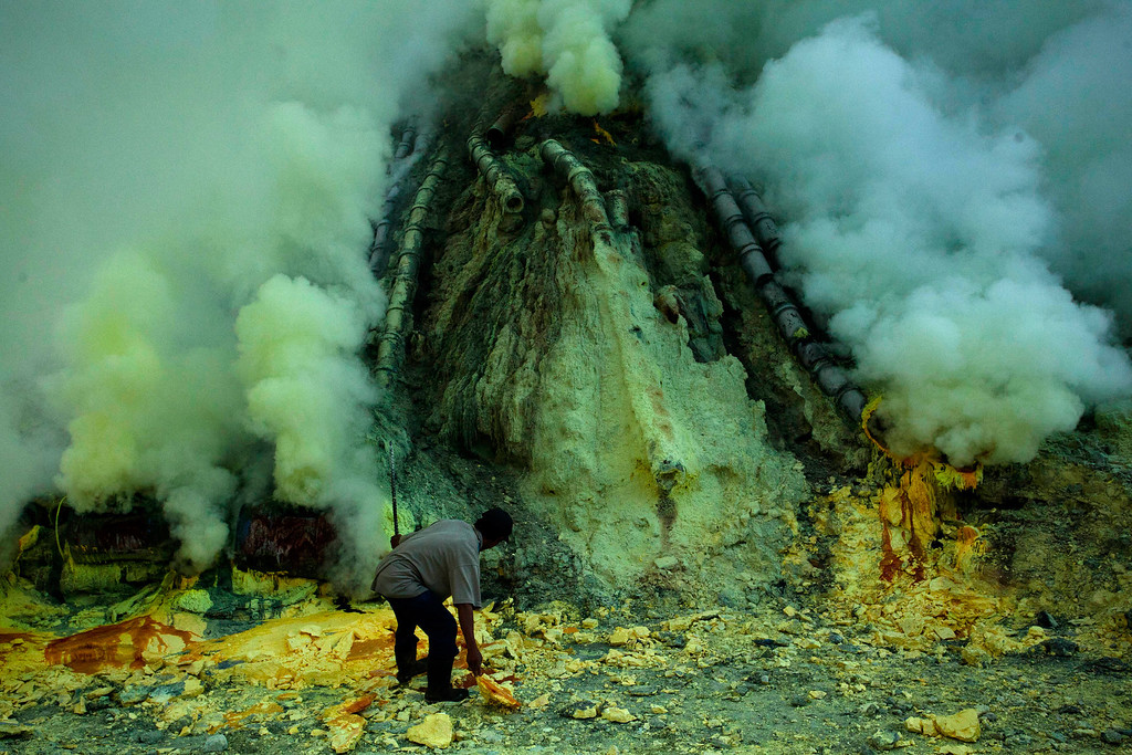 . A miner extracts sulphur from pipe at the flow crater during an annual offering ceremony on the Ijen volcano on December 17, 2013 in Yogyakarta, Indonesia. (Photo by Ulet Ifansasti/Getty Images)