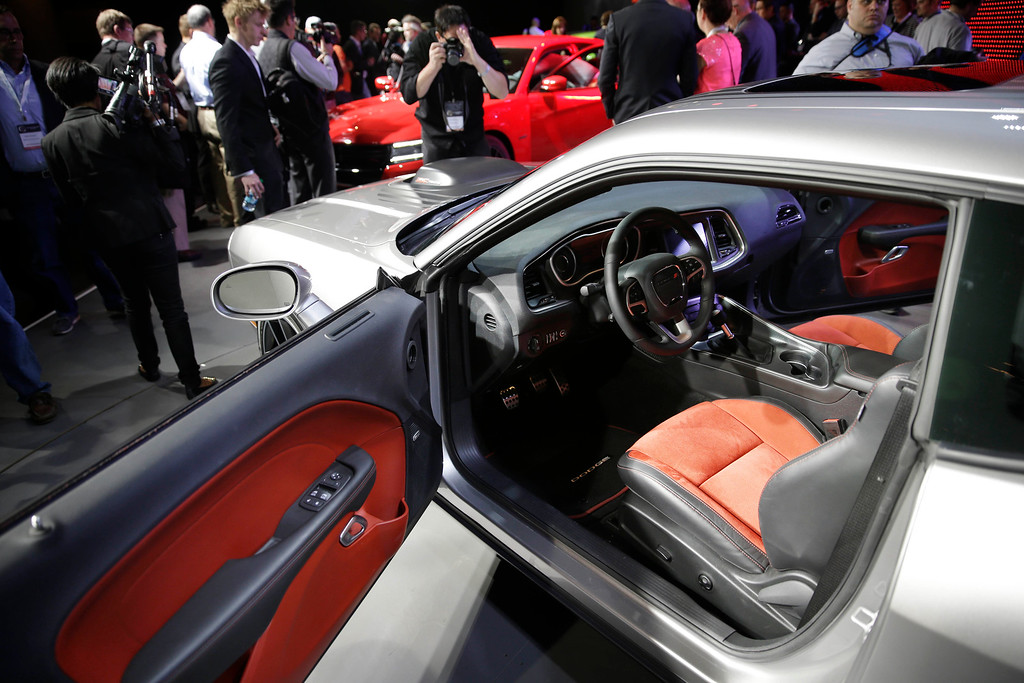 . Poeple gather around a 2015 Dodge Challenger after it is introduced at the New York International Auto Show in New York, Thursday, April 17, 2014.  (AP Photo/Seth Wenig)