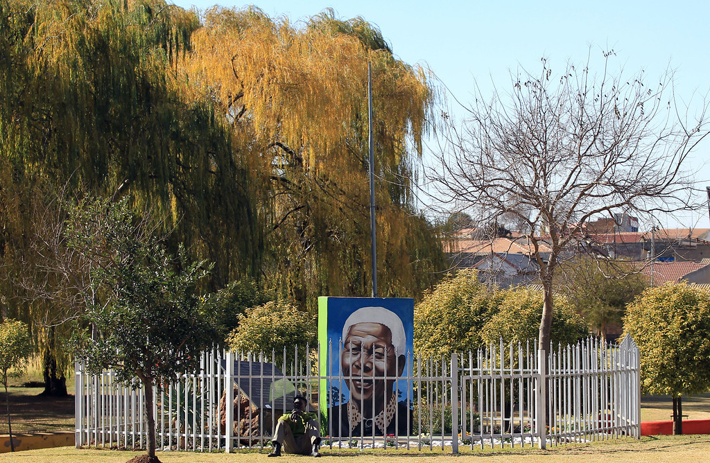 . Unidentiified man sits next to a mural of the former South African President Nelson Mandela at Thokoza Park, Soweto township in Johannesburg, South Africa, Sunday, June 25, 2013.  South Africa\'s president Jacob Zuma on Tuesday urged his countrymen to show their appreciation for Nelson Mandela, who is in critical condition in a hospital, by marking his 95th birthday next month with acts of goodness that honor the legacy of the anti-apartheid leader. (AP Photo/Themba Hadebe)
