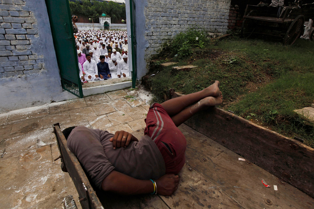 . A laborer sleeps on a push cart as Indian Muslims offer prayers during Eid al-Adha in Allahabad, India, Wednesday, Oct. 16, 2013.  (AP Photo/Rajesh Kumar Singh)