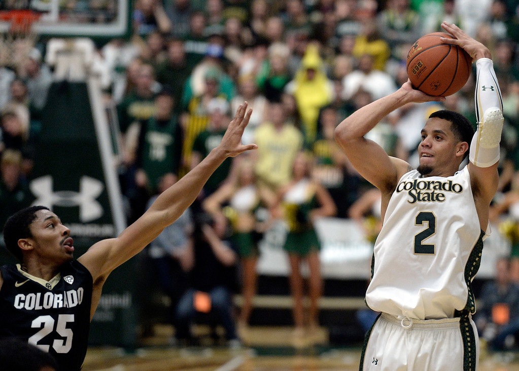 . CSU\'s  Marcus Holt takes a shot over Spencer Dinwiddie during an NCAA game against CU on Tuesday, Dec. 3, 2013, at the Moby Arena in Fort Collins.