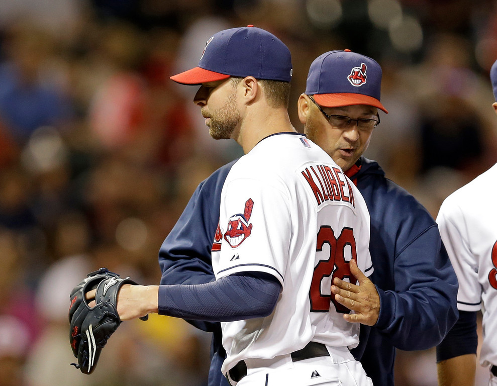 . Cleveland Indians starting pitcher Corey Kluber (28) gets a slap on the back from manager Terry Francona as he leaves a baseball game against the Colorado Rockies in the eighth inning Friday, May 30, 2014, in Cleveland. (AP Photo/Mark Duncan)