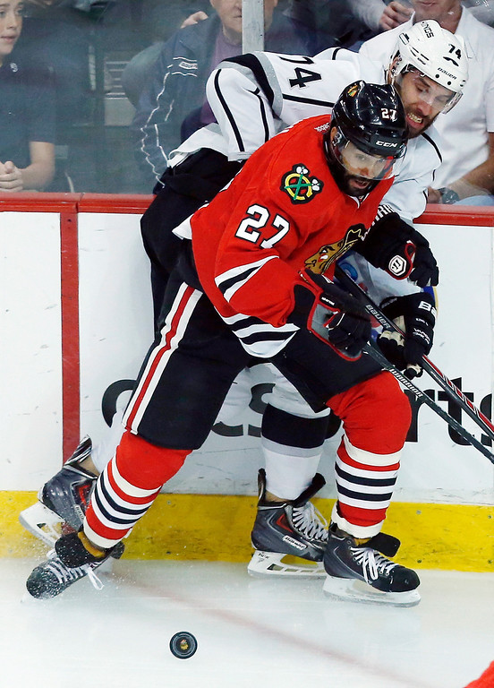 . Chicago Blackhawks defenseman Johnny Oduya (27) and Los Angeles Kings left wing Dwight King (74) battle for the puck during the first period in Game 5 of the Western Conference finals in the NHL hockey Stanley Cup playoffs Wednesday, May 28, 2014, in Chicago. (AP Photo/Andrew A. Nelles)