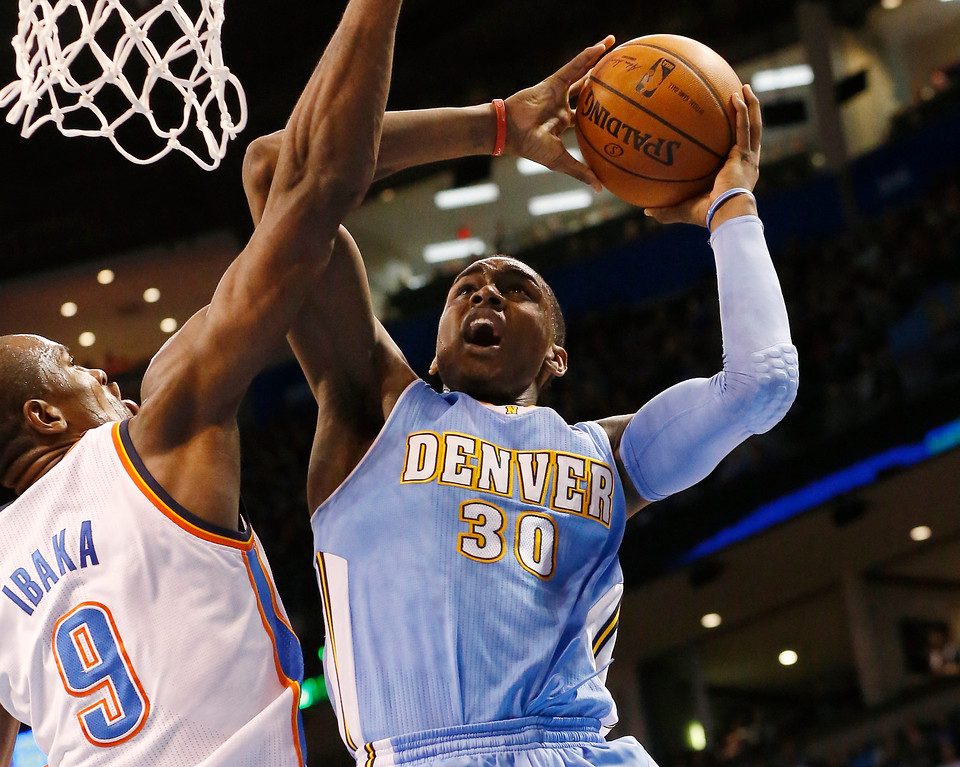 . Denver Nuggets forward Quincy Miller (30) shoots as Oklahoma City Thunder forward Serge Ibaka (9) defends in the second quarter of an NBA basketball game in Oklahoma City, Monday, March 24, 2014. (AP Photo/Sue Ogrocki)