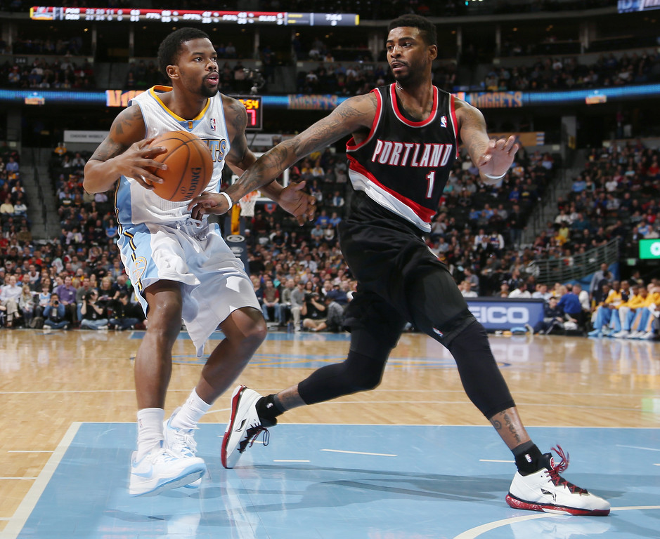 . Denver Nuggets guard Aaron Brooks, left, drives for a shot as Portland Trail Blazers forward Dorell Wright covers in the third quarter of an NBA basketball game in Denver, Tuesday, Feb. 25, 2014. Portland won 100-95. (AP Photo/David Zalubowski)
