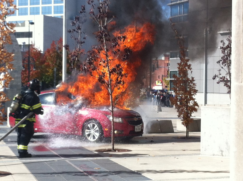 . Denver Fire works on putting out a car fire outside the Wellington Webb Building, November 07, 2013. The car was on fire parked in the middle of the building plaza walkway in downtown Denver. (Photo By Lance Hernandez/7 News)