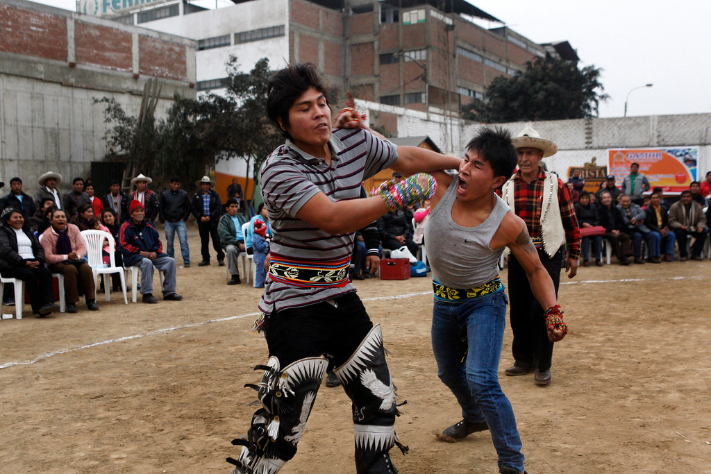 . Eber Sabina, right, and Sebastiano Mendoza take punches during a Takanakuy ritual fight in Lima, Peru. It is a relative of a custom that people in the highlands of neighboring Bolivia call Tinku. (AP Photo/Karel Navarro)