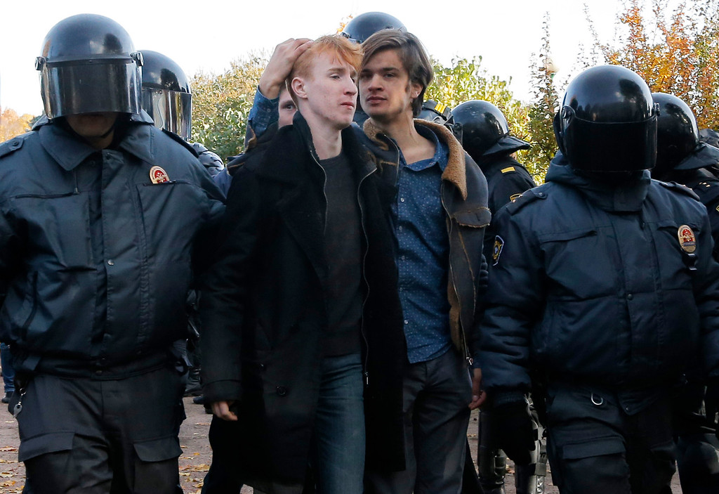 . Riot police detain gay rights activists after a scuffle with anti-gay protesters during an LGBT rally in St. Petersburg, Russia, Saturday, Oct. 12, 2013. A gay rights rally in St. Petersburg has ended in scuffles after several dozen protesters were confronted by about 200 conservative and religious activists. The police standing nearby waited until clashes broke out between the two groups before intervening. According to Russian news agencies, the police detained 67 people from both sides. (AP Photo/Dmitry Lovetsky)