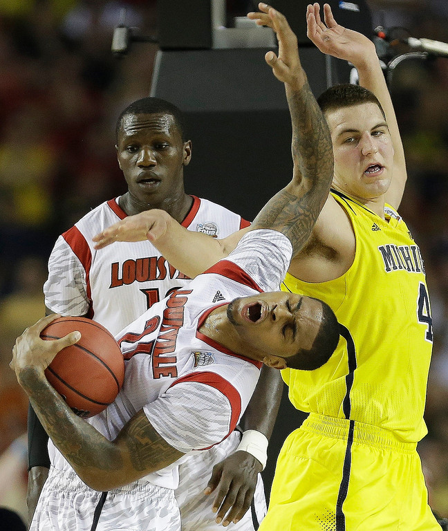 . Louisville forward Chane Behanan (21) grabs the ball as Michigan forward Mitch McGary (4) looks on during the first half of the NCAA Final Four tournament college basketball championship game Monday, April 8, 2013, in Atlanta. (AP Photo/Charlie Neibergall)