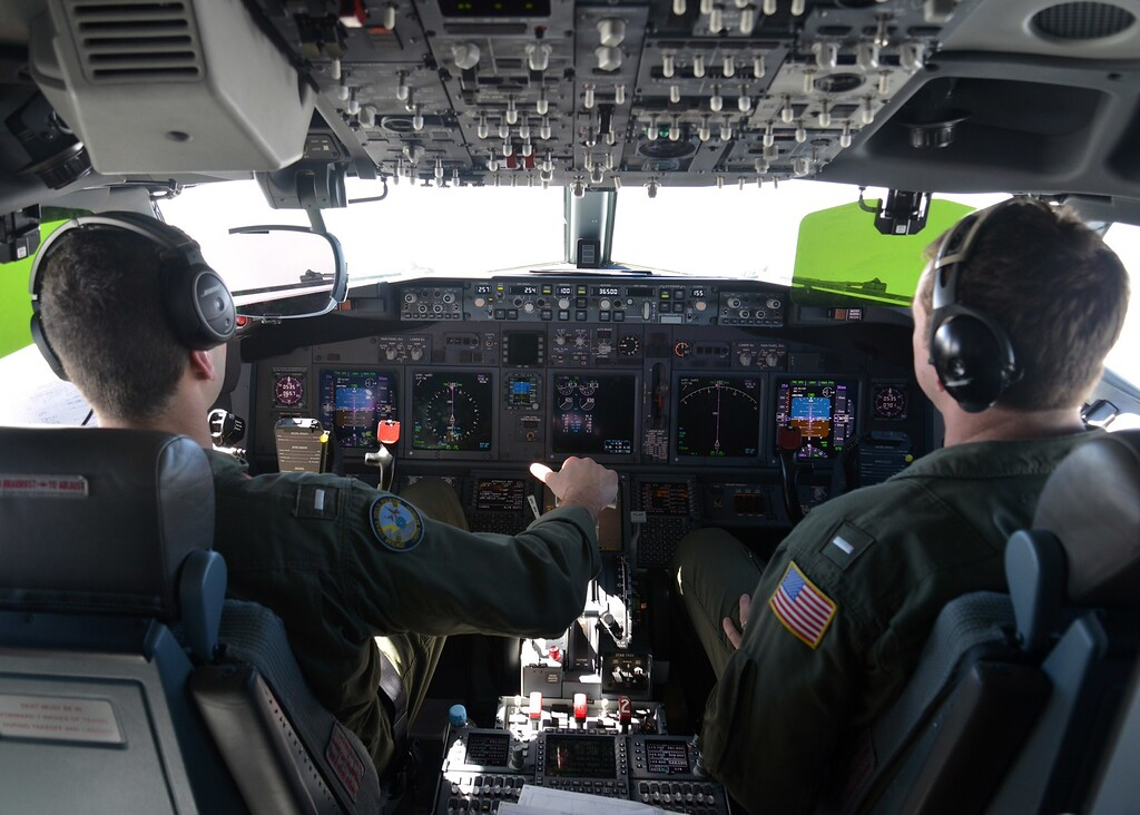 """. This handout photo taken on March 19, 2014 and released on March 20, 2014 by the US Navy shows Lt. j.g. Kyle Atakturk (L) and Lt. j.g. Nicholas Horton (R), naval aviators assigned to Patrol Squadron (VP) 16, piloting a P-8A Poseidon plane in air over the waters of the Indian Ocean during a mission to assist in search and rescue operations for Malaysia Airlines flight MH370, part of the assistance by the US 7th Fleet.  Surveillance aircraft scoured a remote and stormy section of the Indian Ocean on March 20, 2014 for a pair of floating objects that Australia and Malaysia guardedly called a \""""credible\"""" lead in the 12-day-old hunt for the missing passenger jet.       AFP PHOTO / US Navy photo by Mass Communication Specialist 2nd Class Eric A. Pastor/Released  /AFP/Getty Images"""