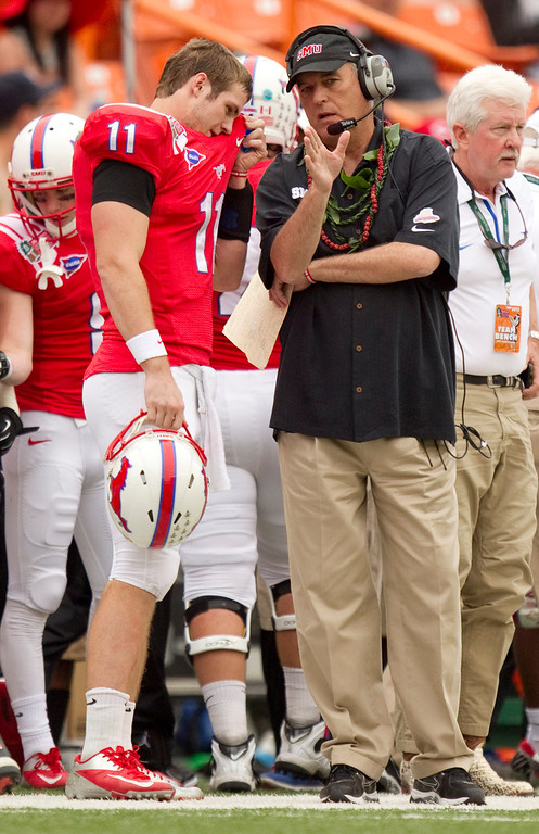 . SMU quarterback Garrett Gilbert (11) listens to coach June Jones in the first quarter against Hawaii in the Hawaii Bowl, an NCAA college football game Monday, Dec. 24, 2012, in Honolulu. (AP Photo/Eugene Tanner)