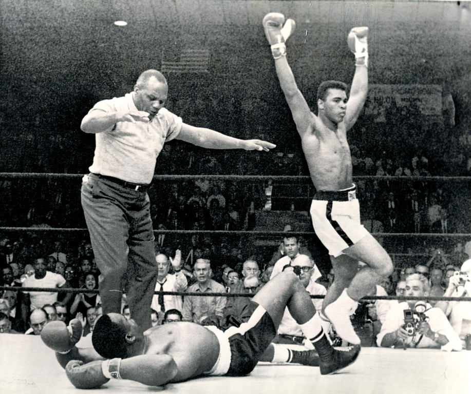 . LEWISTON, Me., May 25--VICTORY DANCE--Heavyweight champion Cassius Clay, arms upraised, begins his victory dance around challenger Sonny Liston after he cut short their scheduled 15-round title bout by knocking him out in one minute of the first round.  Referee Joe Walcott waves his arm ending the bout. 1965. Credit: AP