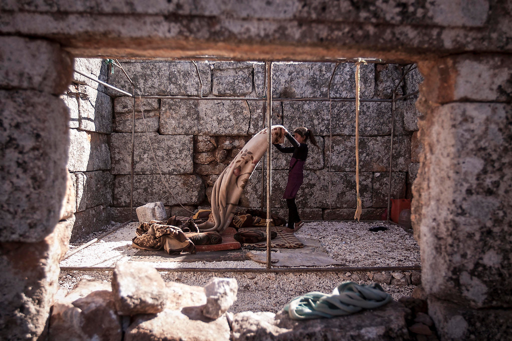. In this Friday, Sept. 27, 2013 photo, a displaced Syrian girl makes her bed after waking up near Kafer Rouma, in ancient ruins used as temporary shelter by those families who have fled from the heavy fighting and shelling in the Idlib province countryside of Syria.(AP Photo)