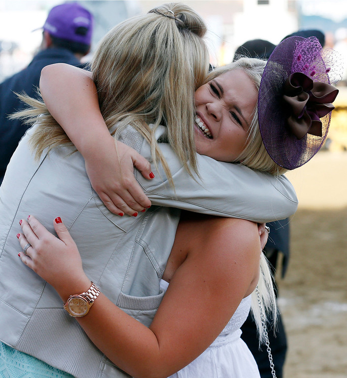. Race-goers celebrate after California Chrome won the 139th Preakness Stakes horse race at Pimlico Race Course, Saturday, May 17, 2014, in Baltimore.  (AP Photo/Mike Stewart)