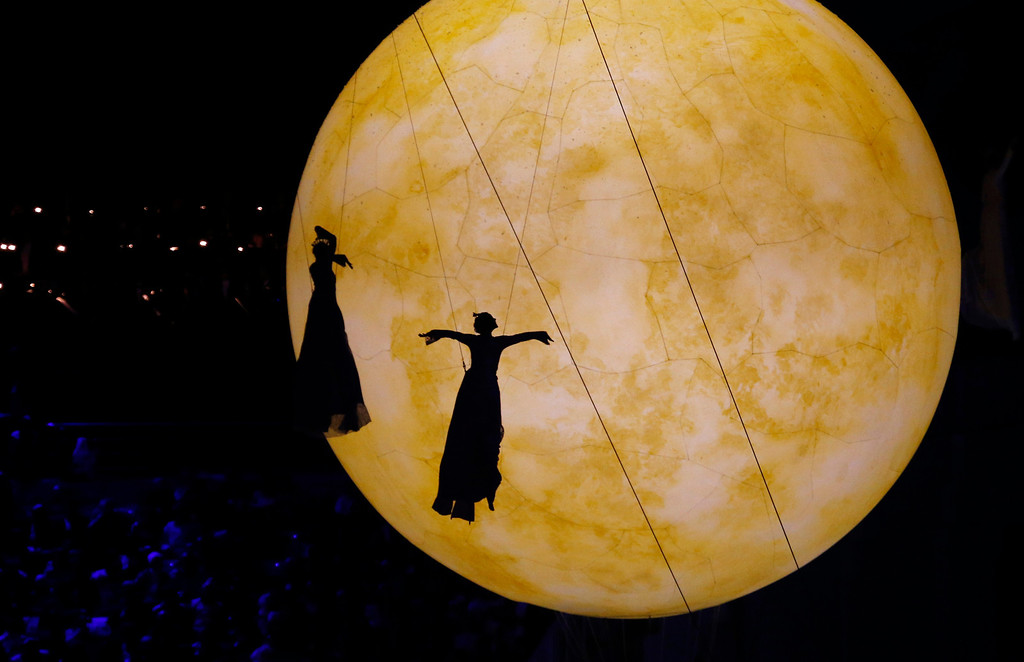. The shadow of artists fall on a giant balloon meant to represent the moon during the closing ceremony of the 2014 Winter Olympics, Sunday, Feb. 23, 2014, in Sochi, Russia. (AP Photo/Dmitry Lovetsky)