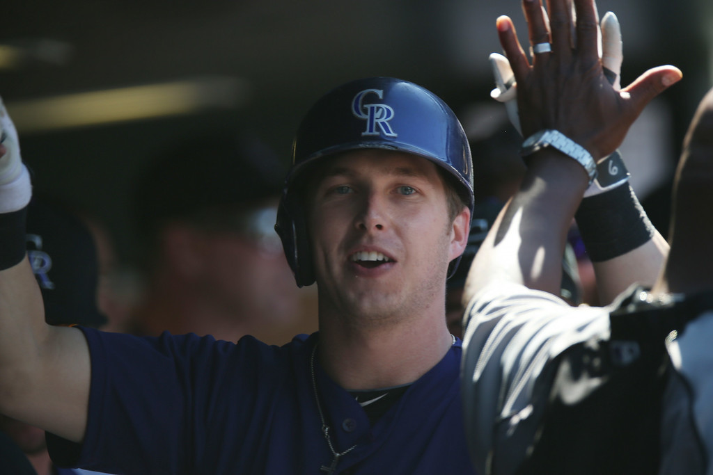 . Colorado Rockies\' Corey Dickerson is congratulated after hitting a solo home run against the San Francisco Giants in the fifth inning of the Rockies\' 9-2 victory in a baseball game in Denver, Wednesday, Sept. 3, 2014. (AP Photo/David Zalubowski)
