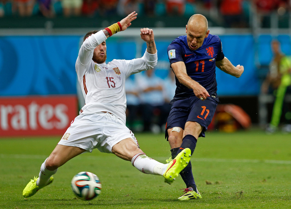 . Netherlands\' Arjen Robben kicks the ball past Spain\'s Sergio Ramos to score his side\'s second goal during the second half of the group B World Cup soccer match between Spain and the Netherlands at the Arena Ponte Nova in Salvador, Brazil, Friday, June 13, 2014. (AP Photo/Wong Maye-E)