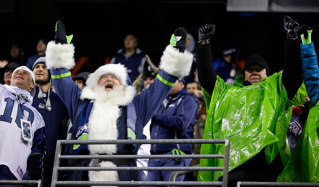 . A Seattle Seahawks fan dressed as Santa celebrates a play against the New Orleans Saints during an NFL football game, Monday, Dec. 2, 2013, in Seattle. (AP Photo/Scott Eklund)