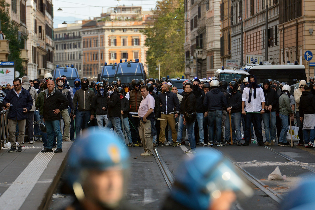 . A group of men from the CasaPound (a social center of fascist inspiration) faces anti-riot policemen as thousands of people take part in an anti-austerity protest on October 19, 2013 in Rome. Between 3,000 and 4,000 police officers have been deployed, Italian media reports said, and protest organizers say they expect more than 20,000 to join. ALBERTO PIZZOLI/AFP/Getty Images