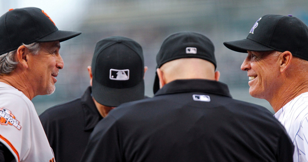 . San Francisco Giants bench coach Ron Wotus, left, and Colorado Rockies bench coach Tom Runnells, right meet with the umpires before the first inning of a baseball game, Wednesday, Aug. 28, 2013, in Denver. (AP Photo/Barry Gutierrez)