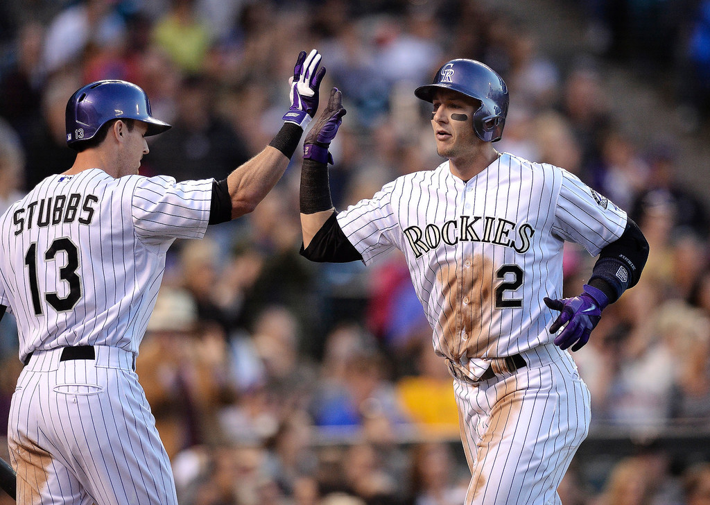 . Troy Tulowitzki accepted congratulations from Drew Stubbs after he crossed the plate on a double by Wilin Rosario in the fourth inning. The Rockies took a 1-0 lead on the play.  (Photo by Karl Gehring/The Denver Post)