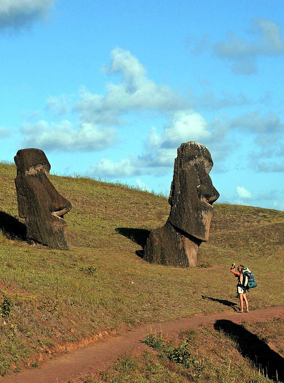 . A tourist takes pictures of Moais monoliths in the Rano Raraku volcano area in Easter Island, 3700 km off the coast of Chile, 12 February 2005. The Chilean island, located in the Polynesian archipelago, has many archeological sites and its Rapa Nui National Park is included on UNESCO\'s World Heritage Site list since 1995.   MARTIN BERNETTI/AFP/Getty Images