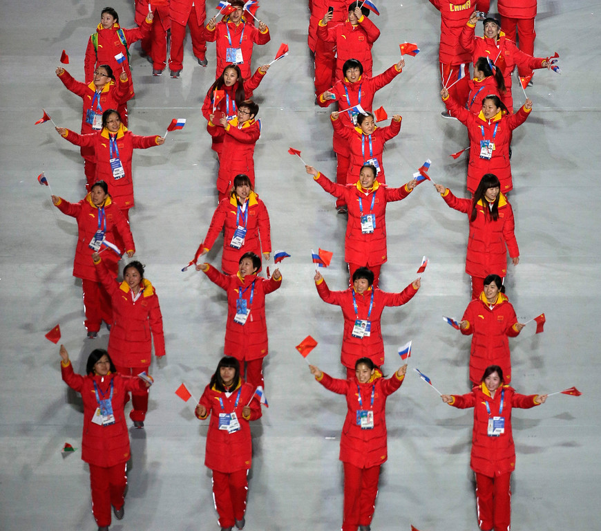 . The Chinese team members wave their national flag and walk in the stadium during the opening ceremony of the 2014 Winter Olympics in Sochi, Russia, Friday, Feb. 7, 2014. (AP Photo/Charlie Riedel)