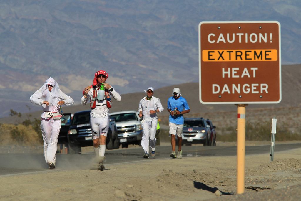 . Runners pass a heat danger warning sign during the AdventurCORPS Badwater 135 ultra-marathon race on July 15, 2013 in Death Valley National Park, California. Billed as the toughest footrace in the world, the 36th annual Badwater 135 starts at Badwater Basin in Death Valley, 280 feet below sea level, where athletes begin a 135-mile non-stop run over three mountain ranges in extreme mid-summer desert heat to finish at 8,350-foot near Mount Whitney for a total cumulative vertical ascent of 13,000 feet. July 10 marked the 100-year anniversary of the all-time hottest world record temperature of 134 degrees, set in Death Valley where the average high in July is 116. A total of 96 competitors from 22 nations are attempting the run which equals about five back-to-back marathons. Previous winners have completed all 135 miles in slightly less than 24 hours.  (Photo by David McNew/Getty Images)
