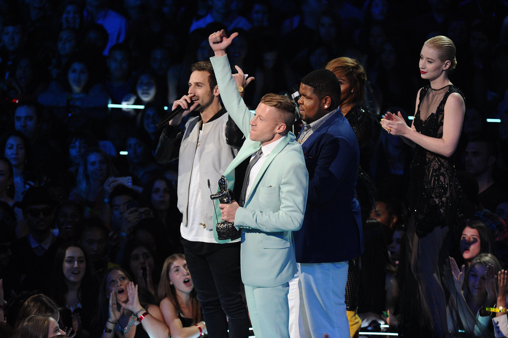 ". Ryan Lewis, left, Macklemore, center, and Ray Dalton accept the award for best hip hop video for ""Can\'t Hold Us\"" as presenters Iggy Azalea, right, and Lil\' Kim look on, at the MTV Video Music Awards on Sunday, Aug. 25, 2013, at the Barclays Center in the Brooklyn borough of New York. (Photo by Charles Sykes/Invision/AP)"