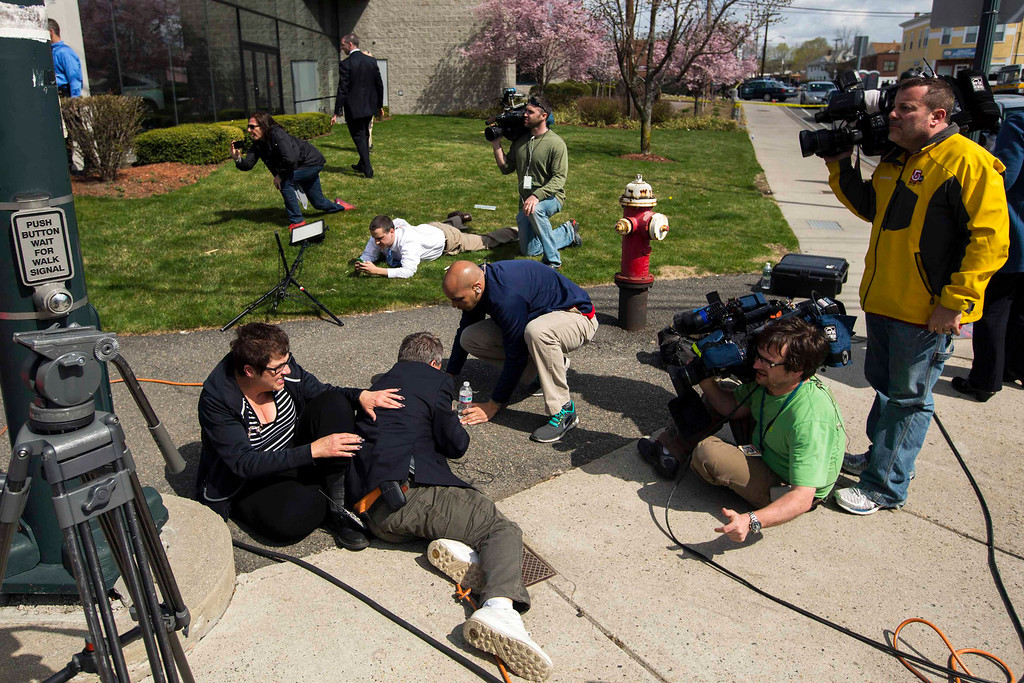 . Members of the media take cover on the instruction of law enforcement officers while covering a police reaction to a suspect on Arsenal St, in the search area for Dzhokar Tsarnaev, the one remaining suspect in the Boston Marathon bombing, in Watertown, Massachusetts April 19, 2013. REUTERS/Lucas Jackson