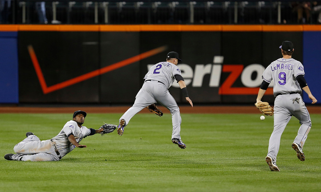 . Colorado Rockies center fielder Dexter Fowler, left, and shortstop Troy Tulowitzkiin (2) miss the play after colliding in center field as second baseman DJ LeMahieu (9) looks on in the third inning of a baseball game against the New York Mets at Citi Field, Tuesday, Aug. 6, 2013, in New York. (AP Photo/John Minchillo)
