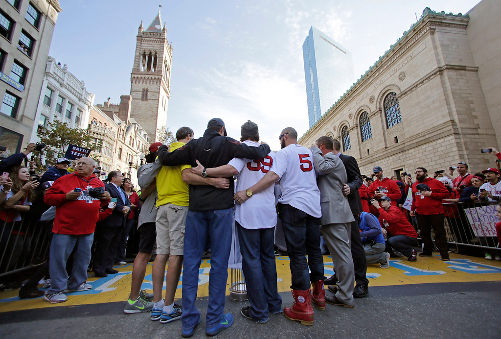 . Boston Red Sox\'s Jonny Gomes (5) and Jarod Saltalamacchia (39) embrace at the finish line of the Boston Marathon, with people affected by the April 2013 bombings,  during a parade in celebration of the baseball team\'s World Series win, Saturday, Nov. 2, 2013, in Boston. (AP Photo/Charles Krupa)