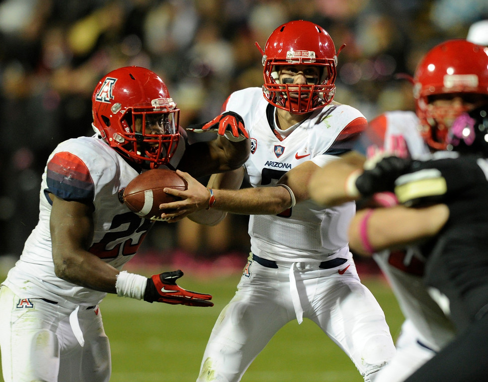 . BOULDER, CO. - OCTOBER 26: Arizona quarterback B.J. Denker handed the ball to tail back Ka\'Deem Carey (25) in the second half. The University of Colorado football team hosted Arizona Saturday night, October 26, 2013. Photo By Karl Gehring/The Denver Post